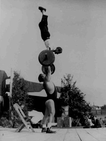 Weightlifter Doug Hepburn balancing a 145lb man atop a 205lb bar