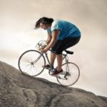 overweight-woman-biking-up-steep-slope
